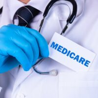 bigstock-Doctor-Holding-A-Card-With-Med-351146876.jpg