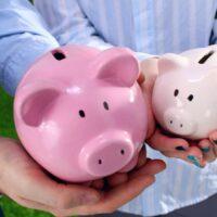 bigstock-Piggy-Bank-in-hands-of-a-famil-104028596.jpg