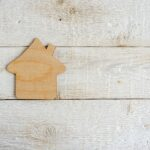bigstock-Toy-House-On-A-Wooden-Backgro-391548308.jpg